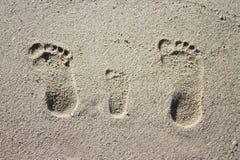 在沙子的三个家庭脚印 免版税库存图片
