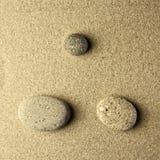 在沙子的三块石头 库存图片