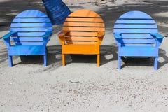 在沙子的三张明亮的色的海滩睡椅与底下拷贝s 免版税库存照片