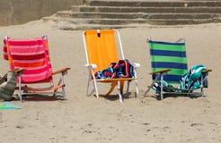 在沙子的三把五颜六色的椅子,在海滩附近 免版税库存图片