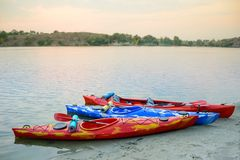 在沙子的三艘移动的皮船靠岸靠近美丽的河或湖晚上 旅行和冒险概念 库存图片
