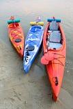 在沙子的三艘移动的皮船靠岸靠近美丽的河或湖晚上 旅行和冒险概念 免版税库存图片