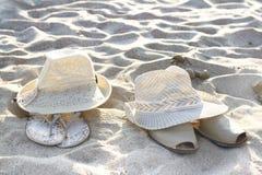 在沙子的两句帽子和凉鞋谎言 库存图片