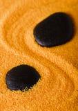 在沙子的两块黑熔岩石头 库存图片