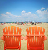 在沙子的两张橙色海滩睡椅 图库摄影