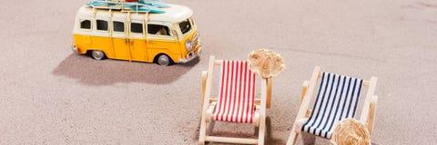 在沙子的两张空的海滩睡椅,与老搬运车 库存图片
