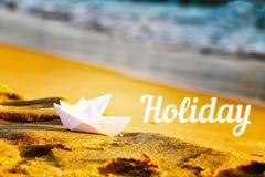 在沙子的两艘纸白色船在海附近 反对沙子和海背景的题字假日  库存照片