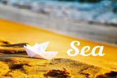 在沙子的两艘纸白色船在海附近 海的题字以沙子和海为背景的 免版税库存图片