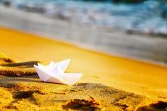 在沙子的两艘纸白色船在海附近 白色制作origami手工制造在波浪背景的海滩  库存图片