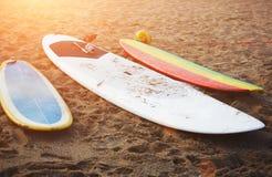在沙子的五颜六色的冲浪板,与最好的朋友的夏时 免版税库存图片