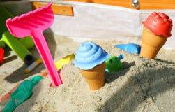 在沙子的五颜六色的玩具在太阳下 与如此的木沙盒 免版税库存照片