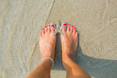 在沙子的人脚与海星 免版税库存图片