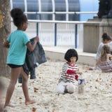在沙子的儿童游戏在泰晤士南银行夏时的 库存照片