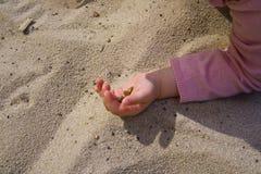 在沙子的儿童的手,当使用时 库存照片