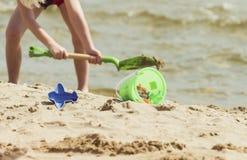 在沙子的儿童红色刀片在海滩 免版税库存图片