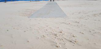 在沙子的具体足迹障碍人们的从海去 免版税图库摄影