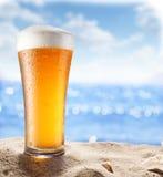 在沙子的冰啤酒玻璃 免版税库存照片