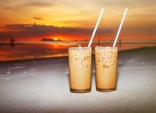 在沙子的冰冻咖啡在日落 免版税图库摄影