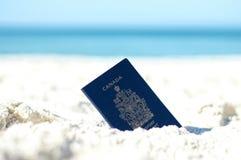 在沙子的加拿大护照在海滩 库存照片