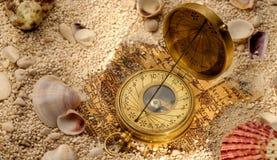 在沙子的古老指南针与贝壳 免版税库存图片
