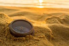 在沙子的古老指南针在海滩日出 免版税库存照片