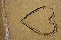 在沙子的可爱的心脏与海洋和海起泡沫在海滩 免版税库存图片