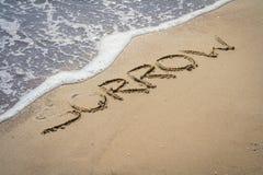 在沙子的哀痛题字 免版税库存图片