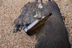 在沙子的啤酒瓶 图库摄影
