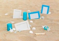 在沙子的四个空白的照片框架靠岸与装饰 图库摄影