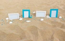 在沙子的四个空白的照片框架靠岸与装饰 库存照片