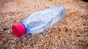 在沙子的塑料瓶 库存照片