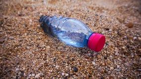 在沙子的塑料瓶 免版税库存照片