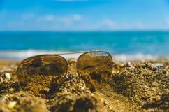 在沙子的太阳镜 免版税库存图片