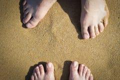 在沙子的女性和男性腿,顶视图 库存图片