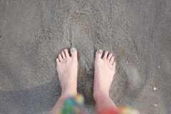 在沙子的女性脚由海 库存照片