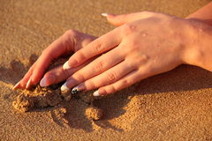 在沙子的妇女手 免版税库存照片