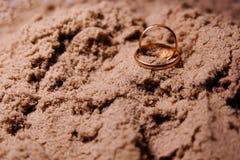 在沙子的婚戒 免版税库存照片