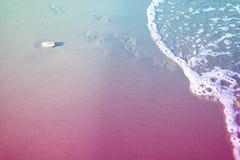 在沙子的孩子的脚印在海滩和cooming的泡沫似的波浪 在光滑的costline的一块白色石头 水平与蓝色和 免版税库存照片