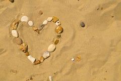 在沙子的小卵石心脏 免版税图库摄影