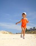 在沙子的小女孩奔跑 库存图片