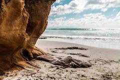 在沙子的岩石峭壁,在与多云天空的一个晴天 库存图片