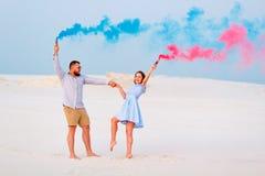 在沙子的年轻夫妇身分和拿着彩色烟幕炸弹,浪漫加上蓝色和红色烟幕弹  库存图片