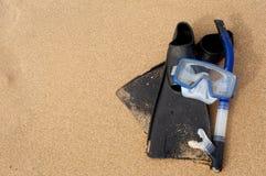 在沙子的废气管屏蔽&鸭脚板在海滩 免版税库存照片