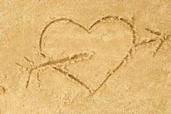 在沙子的心脏和箭头图画 免版税库存图片