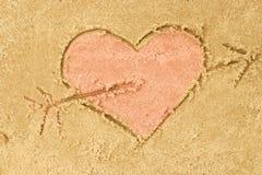 在沙子的心脏和箭头图画 库存照片