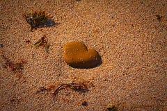 在沙子的心脏石头 免版税图库摄影