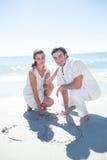 在沙子的愉快的夫妇图画心脏形状 图库摄影