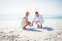 在沙子的愉快的夫妇图画心脏形状 免版税库存照片