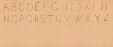 在沙子的手写拉丁字母表与 免版税库存图片