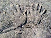 在沙子的手 库存照片